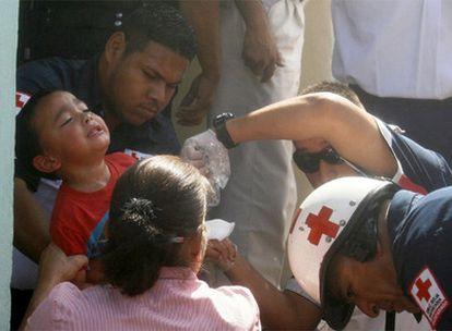 Socorristas de Cruz Roja evacuan a un niño de la guardería.