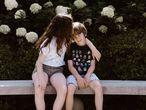 Dos hermanos se sientan juntos en un parque.