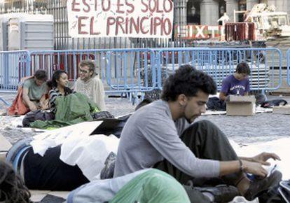 Varios indignados, esta mañana en la Plaza Mayor de Madrid, después de pasar la noche en el lugar y poco antes de ser desalojados.