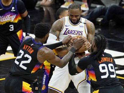 Ayton y Crowder tratan de arrebatarle la pelota a LeBron James.