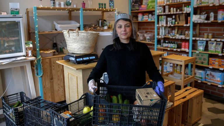 Sara Giacalone holds a basket from a home order at her Cocómero organic products store in Madrid.