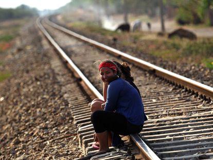 Dos niñas conversan sentadas en las vías del tren en el poblado de Guayacanes.