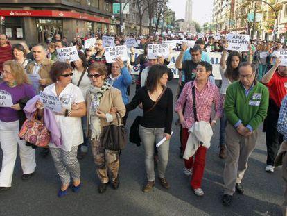 La abogada Jone Goirizelaia (con camisa roja) entre los padres de Iñigo Cabacas, Manuel y Fina Liceranzu, en la manifestación en Bilbao.