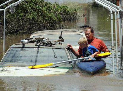 Un padre y su hijo en una canoa junto a vehículos anegados en la ciudad de Bundaberg.