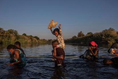 Migrantes haitianos cruzan el lunes el río Grande, en Texas, camino de México.