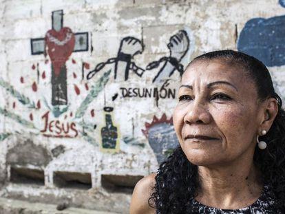 Doris Barrento posa ante el mural que los pandilleros realizaron cuando la firma del acuerdo de convivencia en el barrio de Catuche (Caracas, Venezuela).