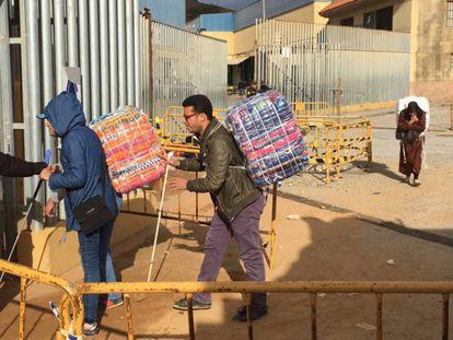 Dos ciegos pasan con sus bultos por el control del polígono situado en la frontera de Ceuta con Marruecos.