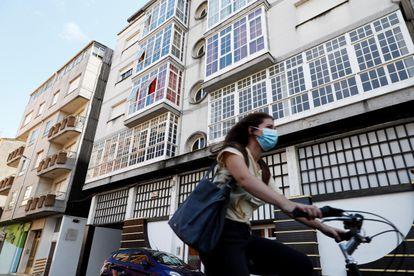 Una mujer monta en bicicleta junto al edificio 41 de la calle Duquesa de Alba, en la localidad lucense de Monforte de Lemos, que ha sido confinado por el Servizo Galego de Saúde.