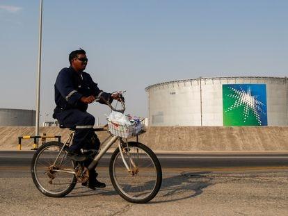 Un empleado pasa en bicicleta cerca de una instalación de Aramco, en Arabia Saudí.