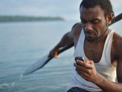 Kelan Sing, un pescador de una isla de Vanuatu, con un teléfono móvil que le permite pedir ayuda mientras faena.