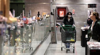 Varias personas hacen la compra en un supermercado en Madrid.