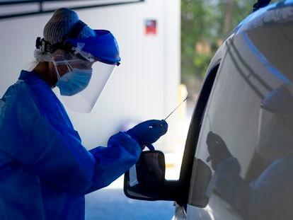 Personal sanitario toma muestras a usuarios, en su propio vehículo, para el test PCR y análisis de coronavirus en el hospital militar de Sevilla.