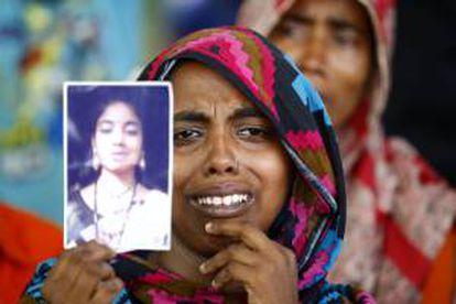 Una mujer muestra el retrato de una familiar víctima del derrumbe durante una oración especial por las víctimas del derrumbe del edificio Rana Plaza, cuando se cumple un año de la tragedia en Savar, Dacca (Bangladesh).