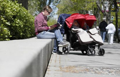Una madre, con sus dos hijos, en un parque de Madrid.