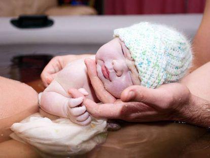 Un bebé recién nacido en el agua. En vídeo, reportaje sobre los paritorios que reducen el número de cesáreas.