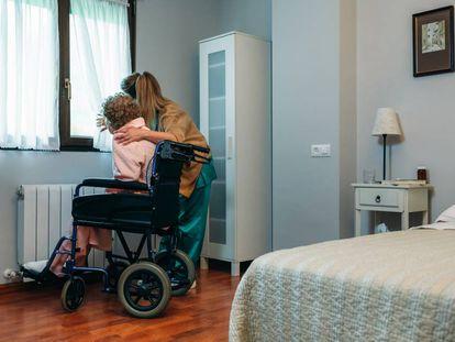 Una cuidadora junto a una anciana en silla de ruedas.