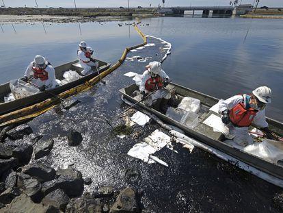 Equipos de limpieza trabajan para mitigar el daño del gran derrame de petróleo en la costa de Huntington Beach, California.
