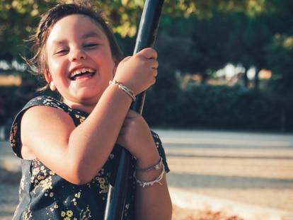 Una niña sonríe mientras se columpia en un parque.