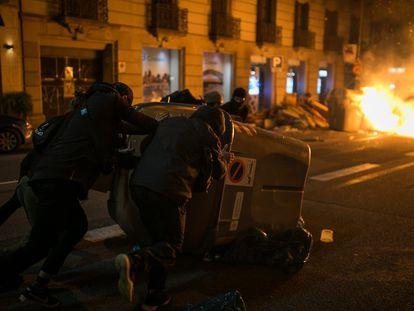 Un grupo de manifestantes mueve un contenedor de basura durante los altercados en el centro de Barcelona, el 17 de febrero.