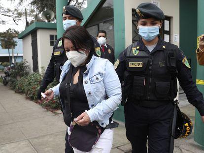 La policía escolta a una de las mujeres detenidas en la fiesta en la que 13 personas fallecieron en una estampida en Lima.