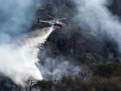 Un helicóptero ayuda en las labores para apagar los incendios en Tepoztlán, Morelos.