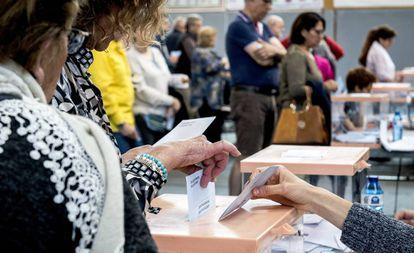 Voto en urna en un colegio electoral.