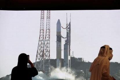 Dos personas observan a través de una pantalla gigante en el Centro Espacial Mohammed bin Rashid, en Dubai, el lanzamiento de un cohete desde Japón, el pasado julio.