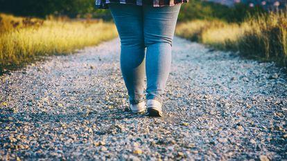 Una chica camina por un sendero empedrado