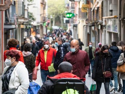 Vecinos de Olot (Girona) pasean por el eje comercial del centro de la ciudad.