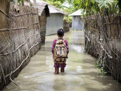 Una niña va al cole en su aldea inundada por lluvias torrenciales en Kurigram (Bangladés).