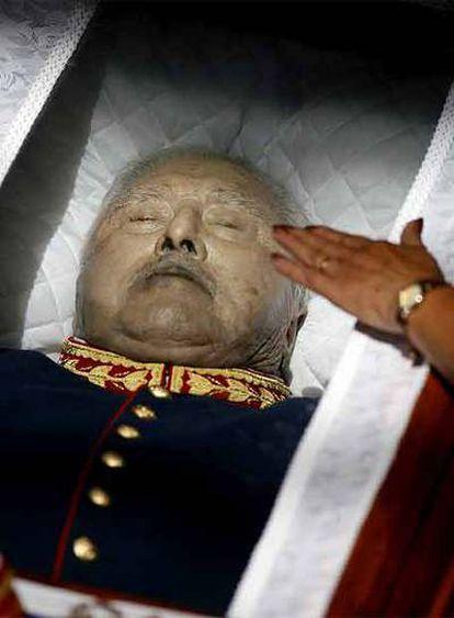Una partidaria de Pinochet toca el vidrio que cubría su cadáver.