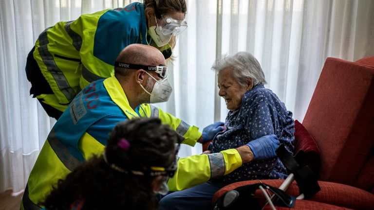 Un equipo sanitario de la UVI atiende a una anciana en su casa de Madrid.