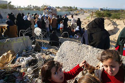 Mujeres y niñas palestinas ante el control militar que separa Muasai del campo de refugiados de Jan Yunis.