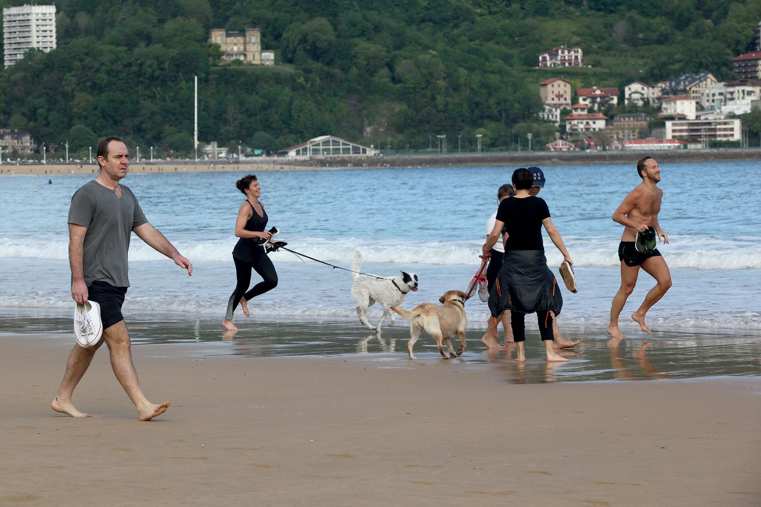Several people walk and run with dogs on La Concha beach on May 2.