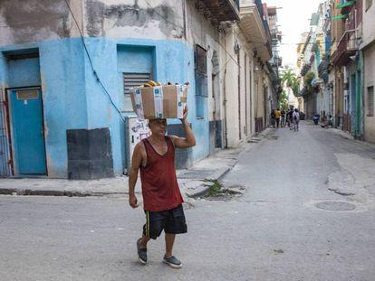 Un hombre camina con una cesta sobre la cabeza, en La Habana.