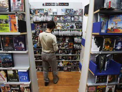Andrés Santana consulta algunos de los 20.000 títulos del videoclub Ficciones de Tirso de Molina.