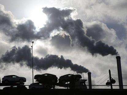 Un camión con coches atraviesa un puente de París ante el humo de una fábrica.