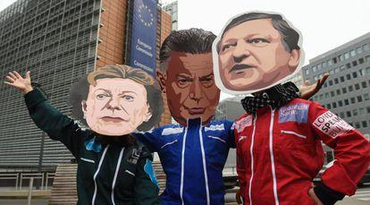 Protesta junto a la Comisión con los rostros de la excomisaria Neelie Kroes, el excomisario Karel De Gucht y el expresidente Barroso.