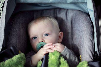 Un bebé viaja en su sillita del coche.