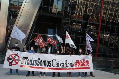 """Varias personas con una pancarta en la que se lee: """"Todos Somos Caixabank, no ERE"""", durante una concentración contra los despidos en la entidad, en las Torres Kio de Plaza de Castilla de Madrid, el 20 de mayo."""