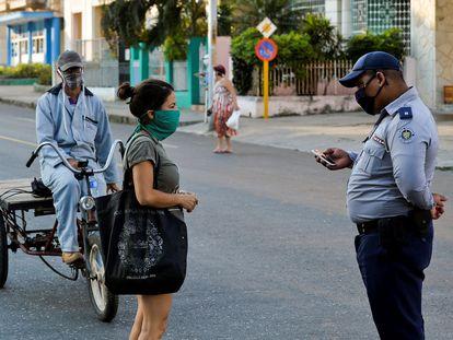 Un policía revisa la identificación de una mujer en La Habana, durante la cuarentena.