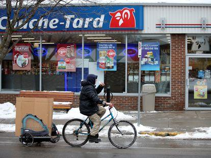 Un ciclista pasa ante una tienda Couche-Tard en Montreal (Canadá).