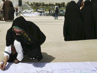 Una mujer firma en un acto en Teherán en apoyo de un acuerdo en las negociaciones nucleares.