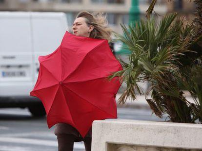Una mujer se protege del viento en San Sebastián.