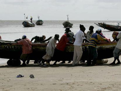 Varios senegaleses arrastran un cayuco, en una playa de Dioghe, una de las localidades de donde parten hacia Canarias. Foto de archivo.