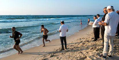 Israelíes religiosos rezan en el año nuevo judío mientras otros corren en una playa de Ashdod.