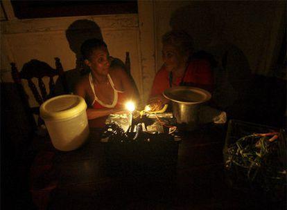 Dos mujeres charlan en la oscuridad en una vivienda de La Habana afectada por un corte de suministro de energía eléctrica.