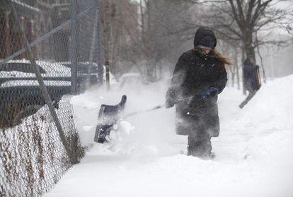 Una mujer limpia de nieve su casa en Detroit (Michigan).