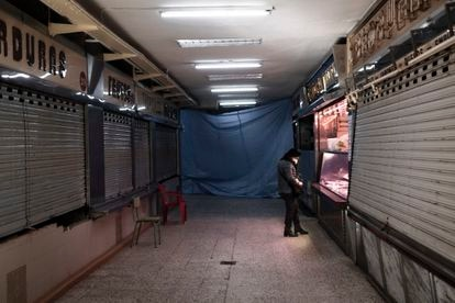 Una mujer saca dinero de su bolso en la galería de la plaza de Quintana, donde solo queda abierta la carnicería Villegas, que también cerrará este sábado ante la construcción del LIDL en el espacio.