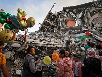 Un hombre palestino vende globos frente a un edificio destruido por los ataques aéreos israelíes, este viernes en Gaza.